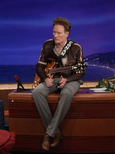 Conan Perches On His Desk During Rehearsal