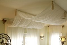 A romantic draped canopy that flows from end to end. An interesting, but elegant look. Click to see our master bedroom makeover ideas.