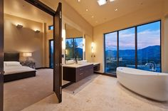 Massive bedroom suite opens into this modern bathroom featuring dark wood cabinetry and vanity with lower makeup space. Large pedestal tub stands before an array of full height windows with mountain views.