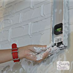 Create faux bricks with drywall mud and level | PlumDoodles.com