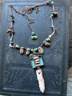 I like the way she incorporates metalwork with natural findings and raku pieces.