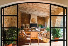 Vistas del porche de piedra a través de puertas de hierro y cristal. La barbacoa