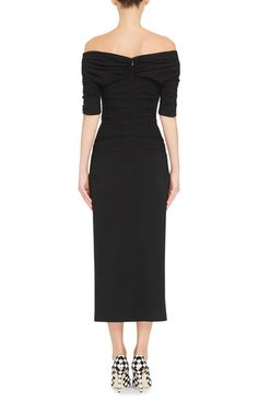 Rendered in virgin wool, this **Dolce & Gabbana** dress features an off the shoulder collar, short sleeves, a fitted bodice, and a pencil midi skirt.