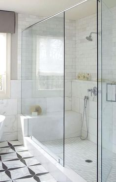 A walk in shower is filled with a mix of marble shower tiles lined with a shower head placed over a built-in marble shower shelf.