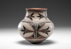 San Ildefonso Polychrome Olla Deaccessioned from a Midwestern Museum, bulbous body with elongated neck and slightly flared rim; bold geometrics decorate jar and rim finished with hatch-marks, height 11.5 in. x diameter 11.5 in. ca 1900