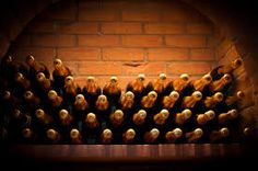 Champagne bottles stacked in a cellar.