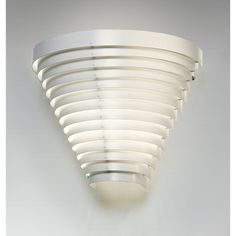 Artek Alvar Aalto - Sconce Designed by Alvar Aalto, this white painted steel sconce adds an interesting design element in addition to illuminating your walls. It projects from the wall this fixture also matches the Aalto ceil.