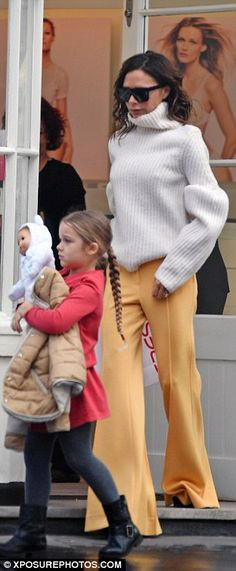 Chic: Teaming it with a white cosy ribbed poloneck jumper, Victoria was well equipped for the rainy weather