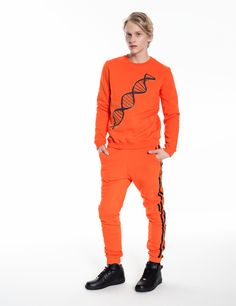 Model is wearing an orange set: Sportivo pants and sweatshirt with DNA chain