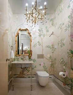 Beautiful taupe hand painted Chinoiserie walls with a hint of metallic in this bathroom. Love the gold Queen Anne mirror, and the tankless toilet and streamlined bamboo-inspired brass chandelier give this traditional idea a modern edge.