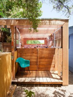 A backyard art shed that serves as a filter between the driveway and the back yard. It creates a light filled space for working on art projects and storing garden tools. One wall and the ceiling are