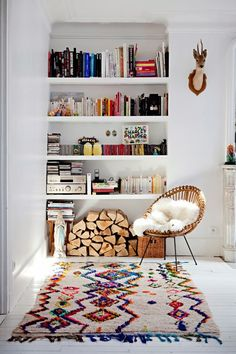 Corner seating area with bookshelves and colorful geo rug.