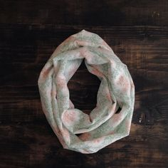 Buffalo Gals Infinity Scarf Wherever you live, you'll look darling in this limited-run infinity scarf handcrafted from reclaimed fabric. Part of our Southern Songbook Collection, this scarf features coral and mint foliage against a white background. Limited run of 15 pieces. Handcrafted in Nashville, TN