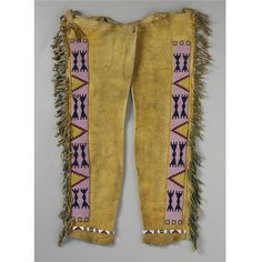 A PAIR OF BLACKFOOT BEADED AND FRINGED HIDE LEGGINGS composed of hide, glass beads, green pigment, cotton thread and sinew.  Length 29 1/4 in.