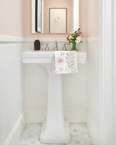 Bright white powder room with @DXVCanada pedestal sink and faucet and @FarrowandBall wallpaper.