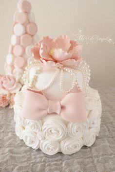 ケーキの下段は、クリームの絞りで作るローズをたっぷり隙間なく♪トップのお花とおリボンはピンクで。そして様々なサイズ、種類のパールをふんだんに入れ込んだ、とっても豪華なクレイケーキです。