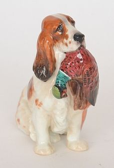 A Royal Doulton model of a brown and white Setter dog holding a pheasant to its mouth, HN1029