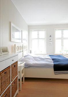 Det smale panelet på soveromsveggen understreker stilen i rommet. Både sengen og kommoden med kurvhyller er kjøpt i Sverige.