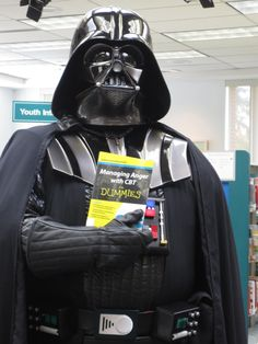 Star Wars Reads Day at Cascades Library. Darth Vader checking out a self help book. For more events visit our page or come to the library,