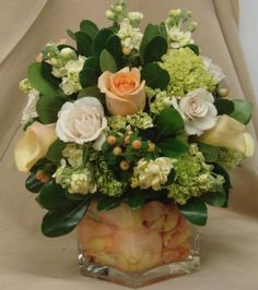 This is a cube vase floral arrangement that features roses, miniature calla lilies and hydrangea in a cream, peach and green color scheme. See our entire selection at www.starflor.com.  To purchase any of our floral selections, as gifts or décor, please call us at 800.520.8999 or visit our e-commerce portal at www.Starbrightnyc.com. This composition of flowers is generally available for same day delivery in New York City (NYC).  SQ163