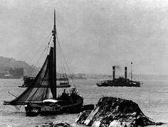 Das Binger Loch ist eine Engstelle des Rheins bei Bingerbrück. Sie war bei den Schiffern gefürchtet wegen ihrer Untiefen und Riffe aus widerstandsfähigem Taunusquarzit. Im Bild ist solch ein Riff zu sehen. Durch Sprengungen sind heutzutage die gefährlichen Stellen teilweise entschärft. Ein großer Radschlepper mit einem geschleppten Schiff fährt auf dem Rhein. In der Nähe eines Riffs liegt ein Aalschocker, ein Schifffür den Aalfang. Drei Boote sind an ihm befestigt