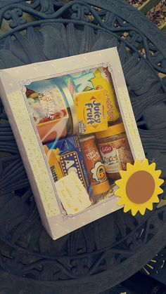 Sunshine box made for grieving neighbors! Used a perfume set box to display the bright colored treats! Contains a dish towel, lemonade packets, candle, skittles, juicy fruit gum, popcorn, popcorn flavoring, and cookie butter! Oh, and a cat toy and treats for their pets!