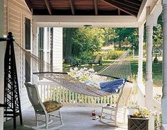 A covered porch with a hammock