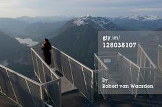 woman on the 5 fingers lookout on Krippenstein mountain looks down on Hallstatt and Obertraun, Austria