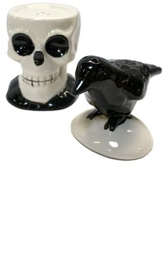 """SKULL/CROW SALT AND PEPPER SET    Price:$13.00    What a perfect pair! This ceramic skull & crow shaker duo will add just enough spice to any meal. Maybe they will just have you scaring up some new recipes too!  6"""" by 5"""" by 3"""""""