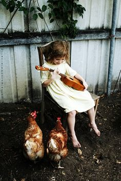 Girl playing music for her chickens