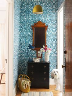 Traditional mirror against bold wallpaper with black chest