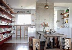 Separado por uma coluna de concreto, este ambiente acrescenta o cinza à decoração, que se destaca como tendência.