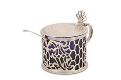 A George III antique sterling silver mustard pot, London 1766, by William Lestourgeon Of circular form, the sides pierced with stylised foliage and geometrical motifs, with scroll handle, shell thumbpiece, the hinged lid engraved with initials, with removale blue glass liner, together with a William IV antique sterling silver Old English pattern mustard spoon, London 1830, by William Chawner II, engraved with a crest. Fully marked to base and lion passant only to lid. (2) Old English, Georgian, Spoon, Mustard, Initials, Shells, Handle, Base, London