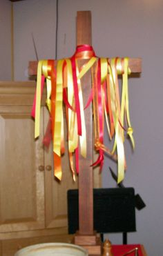"Ribbon lengths, some knotted, of red, orange and yellow (flame colors) on the wooden cross. (We did something similar at a previous church--that cross was about 6 feet tall.) A small fan was trained on the ribbons from the floor in the back for some movement. ""Wind, wind, blow on me."""