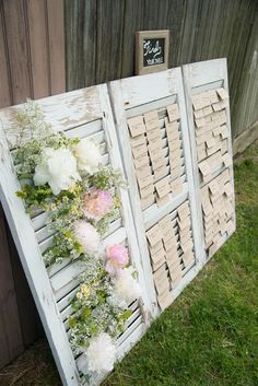 Escort cards in window shutter, accented with florals