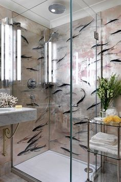 This cool visual effect has been created using bathroom wallpaper behind the frameless glass shower enclosure.
