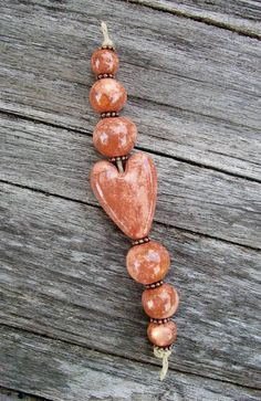 Overall coat of light pink with random coat of darker rose - Rose Granite Heart Strand by Michelle Ann McCarthy.