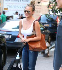 Chrissy Teigen wearing Victoria Beckham sunglasses, J Brand jeans and Chloe bag.