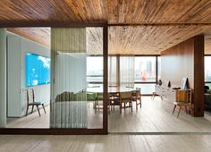 A wooden partition separates the dining room from the living room. The jacaranda table is a vintage find designed by Jorge Zalszupin for L'Atelier. The dining chairs are by the Brazilian designer Sergio Rodrigues and architect Isay Weinfeld designed the sideboard. The fluorescent lamp sculpture on the wall is Luz Natural by Eduardo Coimbra.