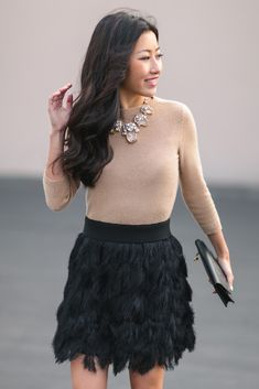 Our black fringe mini skirt is a party outfit must-have. Jean from Extra Petite styles it with a camel crewneck sweater and a sparkly necklace | Banana Republic