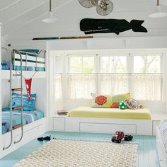 A rainbow of energetic color—sunny yellows, cool blues, and bright reds—coats this happy Rockport, Massachusetts, home designed by Andra Birkerts. A soft turquoise paint (tranquil blue by Benjamin Moore) was applied to the old wood floors in the bunk room Floor paint color