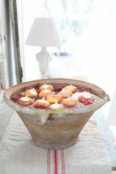 Floating Apple Candle Centerpiece     A beautiful idea for a centerpiece. Cut out apples to fit a votive candle, and place in a beautiful large bowl for floating. Image from Dreamy Whites for more info.