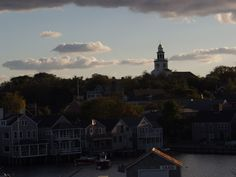 The Nantucket skyline at sunset with the gold domed steeple of the Old North Church and Town Clock on the horizon.