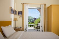A tranquil, impeccably run guesthouse set amid olive groves by the sea, offering delicious home cooking and eco-friendly hospitality Greece Hotels, Hotel Reviews, Windows, Curtains, Rooms, Furniture, Home Decor, Insulated Curtains, Quartos