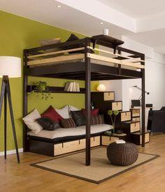 Olivgrünes Schlafzimmer und Wohnzimmer im einem mit vielen bunten Kissen.