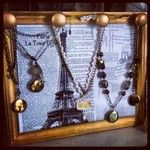 P.S. I made this :P  Gold sprayed vintage frame with knobs, old style photocopy background and voila! Necklace holder!