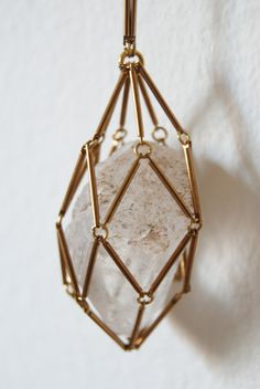 Netting Crystal Cage Necklace by meghannstephenson on Etsy. Quartz crystal wrapped in a netted cage of brass rods. Could probably do the same with long beads on eye-pins.