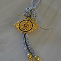 Επίχρυσο γούρι μάτι βυζαντινό με μπλε σμάλτο, δεμένο με γκρι μεταξωτό κορδόνι και μεταλλικά στοιχεία στο τελείωμα.
