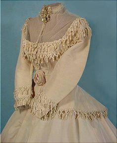 1868 Wedding dress made of heavy silk faille trimmed with chenille. American fitser Alonzo H. Wood, going to the civil war, proposed to his future wife, and both did not know whether he would return. She agreed to wait. Waiting was a long seven years. He survived and in 1868 commissioned the wedding dress for his bride in the studio of Boston.