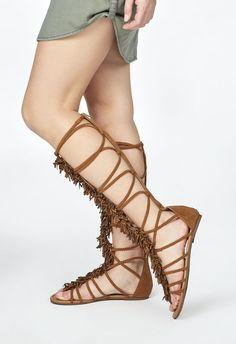 Sandalias romanas muy altas con una particularidad: tienen flecos desde el empeine hasta el extremo superior de la caña. Están en negro y en marrón claro....